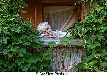 Granny on the green veranda of a village house.