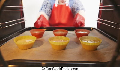 Granny places baking sheet with muffin cupcake silicone...