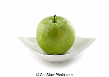 Granny Smith apple on white china plate isolated on white...