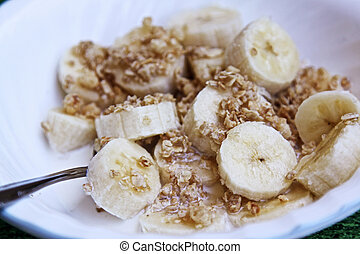 Granola, bananas, cream in a bowl - A spoon in a bowl of...
