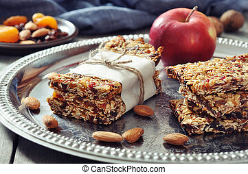 Granola bars on plate with nuts and dried fruits on wooden...