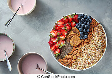 Granola, berries, nuts, chia and yogurt in a plate on a gray concrete background. Ingredients for breakfast. Top view