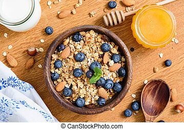Granola bowl with blueberries, almonds and honey on wooden table