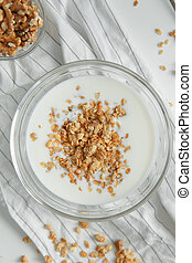 Granola for Breakfast with yogurt and walnuts. Porridge flakes in a bowl with milk.