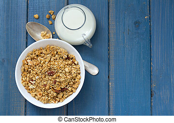 granola in white bowl on blue background