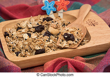 Granola in wooden bowl on white background