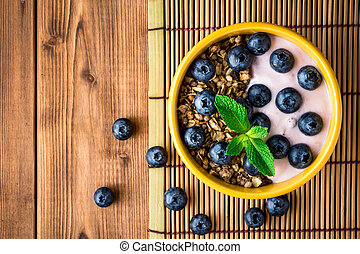 Granola with blueberries and yogurt in yellow bowl on wooden table.