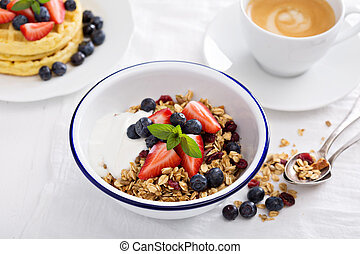 Granola with fresh berries in a bowl on white