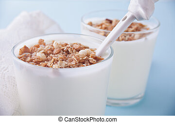Granola with yogurt in glass on a blue table.