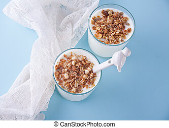 Granola with yogurt in glass on a blue table. Top view