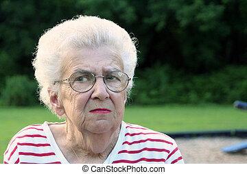 Portrait of senior citizen woman on playground, with suspicious expression.
