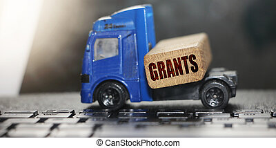 Grants word on wooden block and toy truck with keyboard background. Logistics and transportation management ideas and business commercial concept