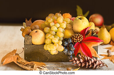 Grape and seasonal fruit in wooden crate on table