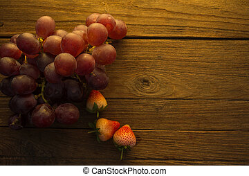 Grape and strawberry on wooden background.
