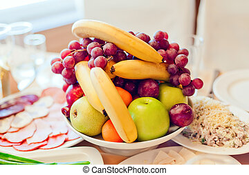 Grape, apples, pears, bananas and other fruits in a vase on a festive table