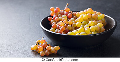 Grape in bowl on a black stone background. Copy space.