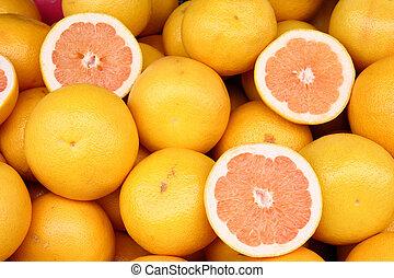 Grapefruit at a market place. Orange coloured fruit background. Natural food.