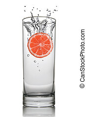 Grapefruit dropped into water glass with splash isolated on white