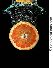 Grapefruit falling into water - Red grapefruit falling into...