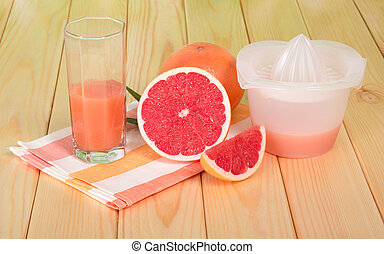 Grapefruit juice in glass, whole fruit and slices on table