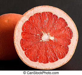 Grapefruit on black stone background