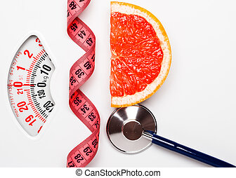 Grapefruit with measuring tape on weight scale. Dieting
