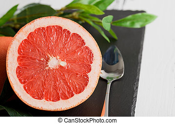 Grapefruit with spoon and leaves on black stone background on white wooden table