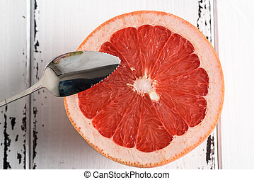 Grapefruit with spoon on white wooden background