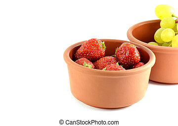 Grapes and strawberries in a bowl, isolated on white