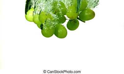 Grapes falling in water on white ba
