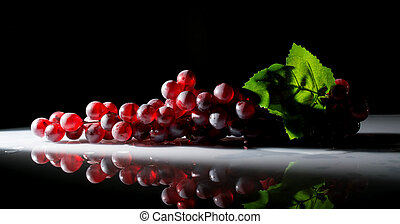 grapes in the sun with splashes of water on a dark background