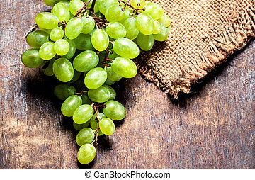 Grapes on a wooden table close up, rustic vintage style with copy space. Fresh grapes on wood. Autumn fruit top view