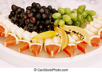 Grapes oranges and other fruits on the plate