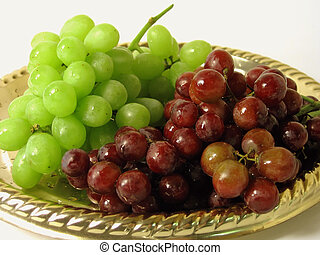 Red and green grapes on gold plate