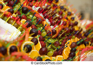 Grapes, strawberries and other exotic fruits pinned with sticks