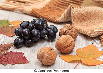 Grapes, walnuts, checkered plaid and dry leaves on wooden boards. An autumn still llife.