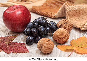 Walnuts, grapes, checkered plaid and dry leaves on wooden boards. An autumn still llife.