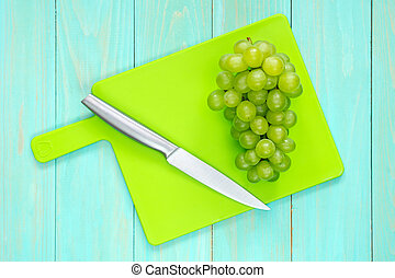 Grapes with a knife on a cutting board