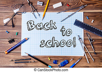 Graph paper with text - back to school and student material on wooden table.