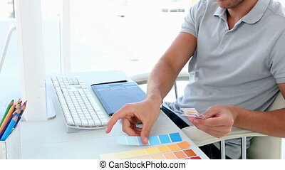 Graphic designer looking at colour samples at his desk in...