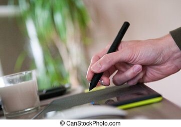 Graphic designer using a drawing graphics tablet