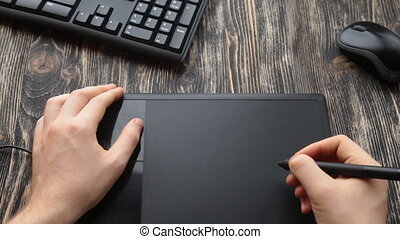 Graphic designer using digital tablet and computer in the ...