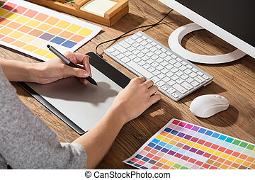 Graphic Designer Using Graphic Tablet With Color Samples On...