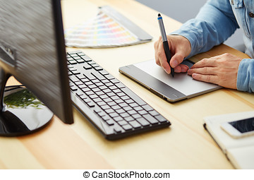 Graphic designer working on a digital tablet in office