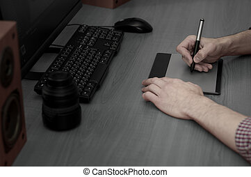 Graphic designer working on digital tablet.