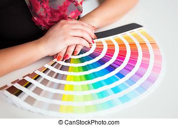 Graphic designer working with cmyk palette in studio