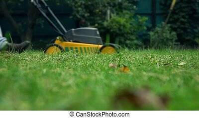 Grass and man with lawnmower. 4K low angle view slow motion shot