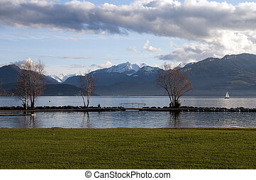 Beach of grass and snowed mountains at Annecy lake on winter, France