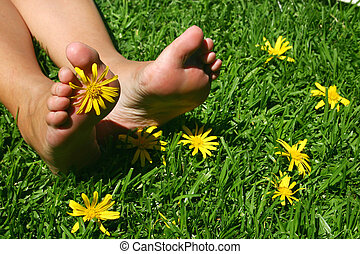Feet on grassy field with yellow daisies