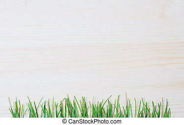 Grass on a background of wooden texture.